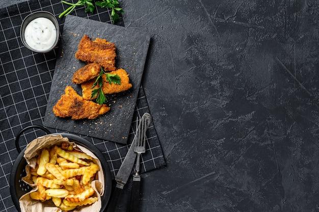 Fish and chips, patatas fritas y filete de bacalao frito en pan rallado