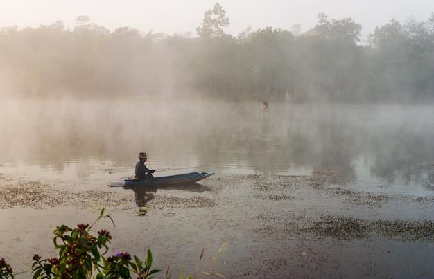Fisheman se sienta en el bote y busca peces en el río
