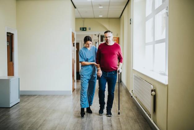 Fisiatra entrenando a un paciente para que vuelva a caminar