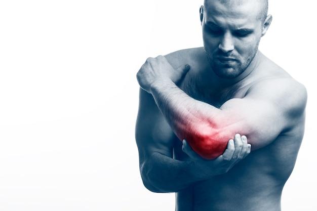 El físico deportivo del hombre sostiene un codo enfermo.