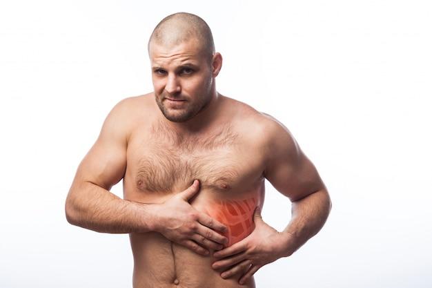El físico juguetón del hombre calvo joven sostiene en costilla dolorida