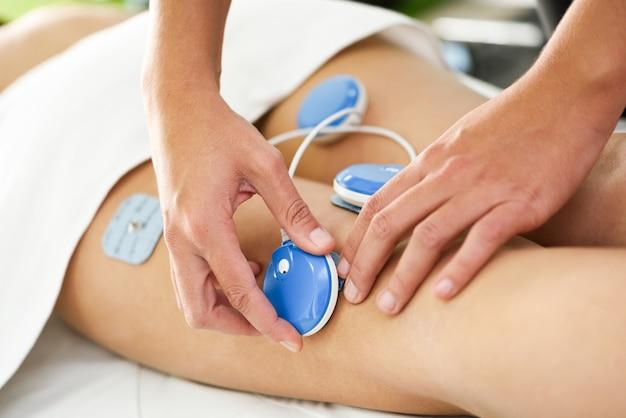 Fisioterapeuta aplicando electro estimulación en fisioterapia a una pierna de mujer joven.