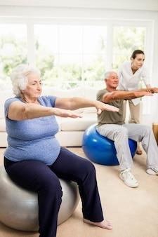 Fisioterapeuta ayudando a pacientes con ejercicios en casa