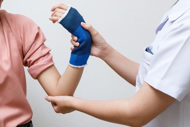 Fisioterapeuta ayudando a su paciente con ejercicio de brazo