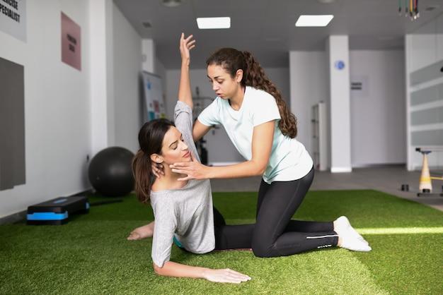 Fisioterapeuta ayudar a la joven mujer caucásica con ejercicio