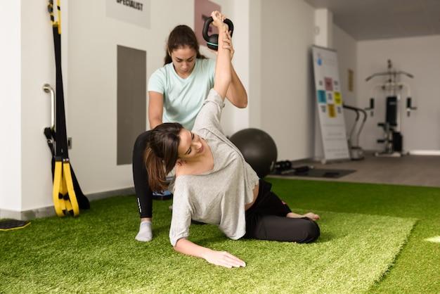 Fisioterapeuta ayudar a la mujer caucásica joven con ejercicio con mancuernas