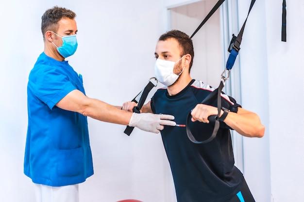 Fisioterapeuta en bata azul con un paciente estirando con gomas al revés. fisioterapia con medidas de protección para la pandemia de coronavirus, covid-19. osteopatía, quiromasaje deportivo