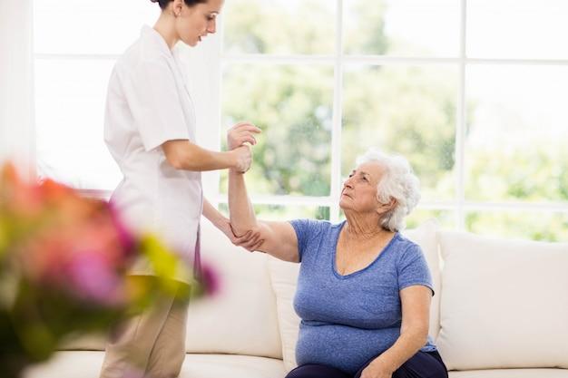 Fisioterapeuta cuidando paciente anciano enfermo en casa