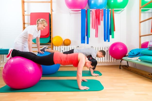 Fisioterapeuta dando ejercicio gimnástico a pacientes.