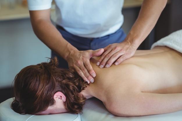 Fisioterapeuta dando masaje de cuello a una mujer