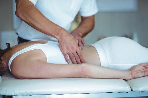 Fisioterapeuta dando masaje de espalda a una mujer