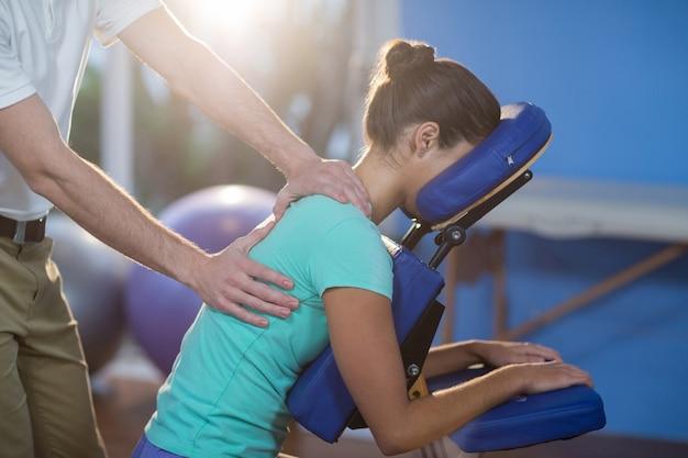 Fisioterapeuta dando masaje de espalda a una paciente