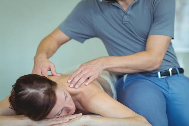 Fisioterapeuta dando masaje de hombro a una mujer