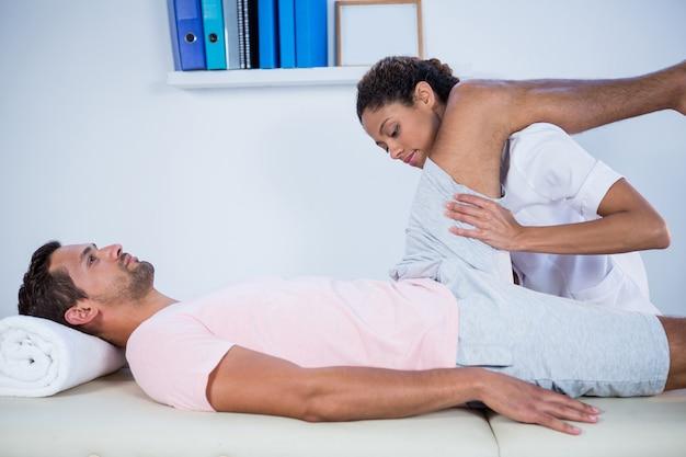 Fisioterapeuta dando masaje de piernas a un paciente