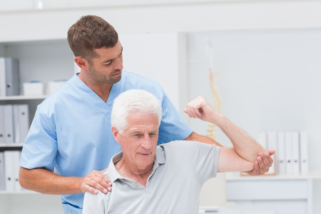 Fisioterapeuta dando terapia física al hombre