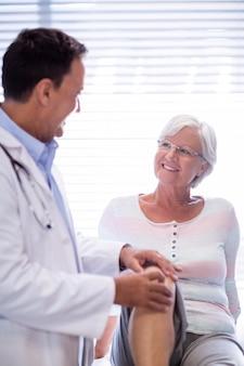 Fisioterapeuta dando terapia de rodilla a mujer senior