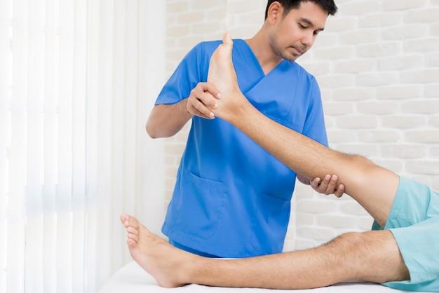 Fisioterapeuta entrenando ejercicio de rehabilitación a paciente masculino en el hospital