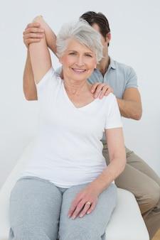 Fisioterapeuta estirando el brazo de una mujer senior sonriente