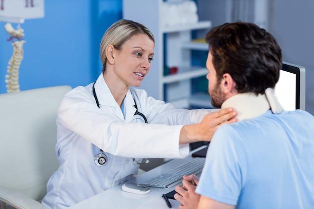 Fisioterapeuta examinando el cuello de un paciente