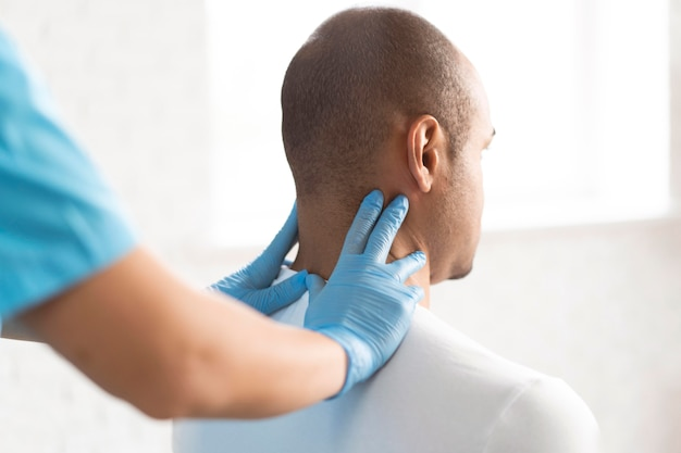 Fisioterapeuta femenina comprobando el cuello del hombre.