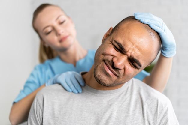 Fisioterapeuta femenina comprobando el dolor de cuello del hombre