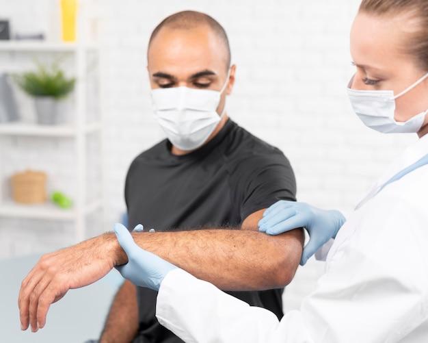 Fisioterapeuta femenina con máscara médica comprobando el codo del hombre