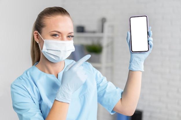 Fisioterapeuta femenina con máscara médica sosteniendo y apuntando al teléfono inteligente