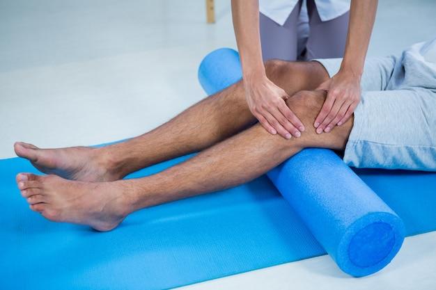 Fisioterapeuta haciendo terapia de piernas a un hombre usando un rollo de espuma