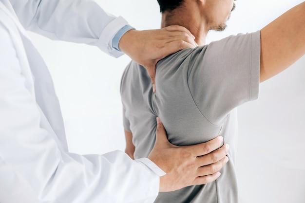 Fisioterapeuta haciendo tratamiento curativo en la espalda del hombre. paciente con dolor de espalda, tratamiento