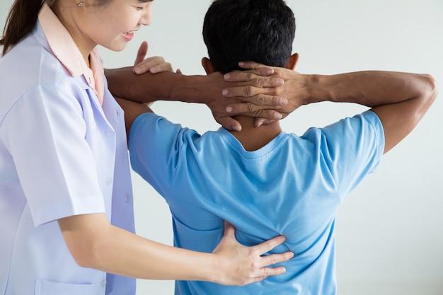 Fisioterapeuta haciendo tratamiento curativo en la espalda del hombre.