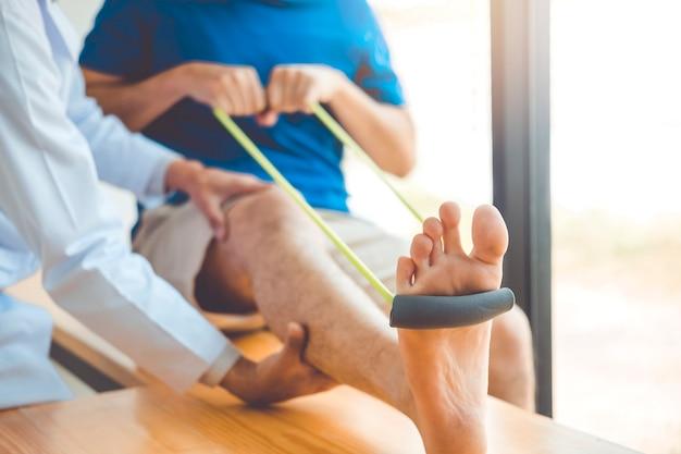 Fisioterapeuta hombre dando resistencia banda ejercicio tratamiento sobre la rodilla de atleta