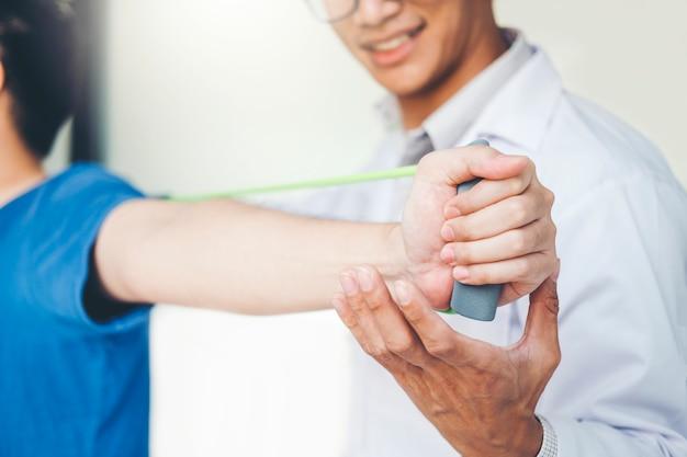 Fisioterapeuta, hombre, tratamiento de ejercicios con banda de resistencia, sobre el brazo y el hombro.
