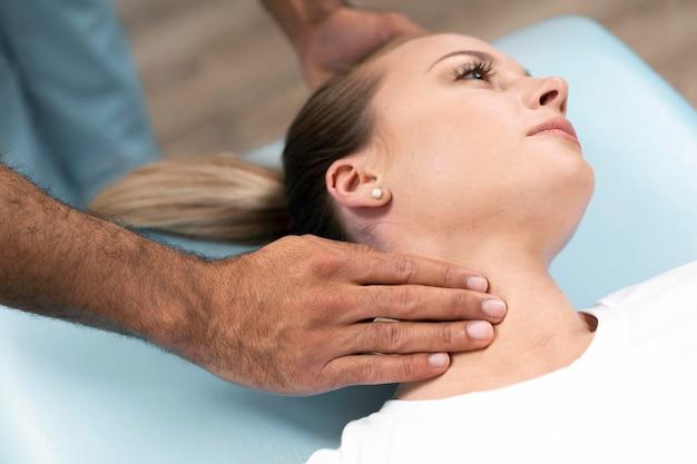 Fisioterapeuta masculino comprobando el cuello de la mujer mientras está sentado en la cama