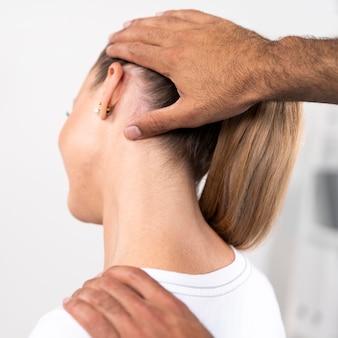 Fisioterapeuta masculino comprobando el cuello de la mujer