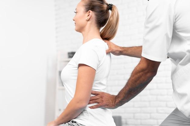 Fisioterapeuta masculino comprobando la espalda de la mujer