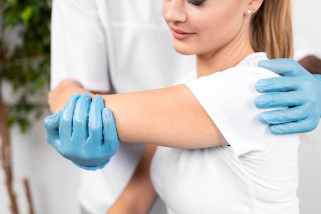Fisioterapeuta masculino comprobando la flexibilidad del hombro de la mujer
