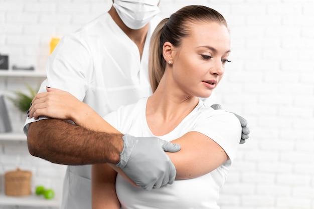 Fisioterapeuta masculino comprobando el hombro de la mujer
