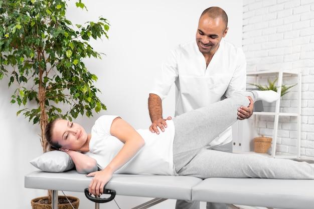 Fisioterapeuta masculino comprobando la movilidad de la cadera de la mujer