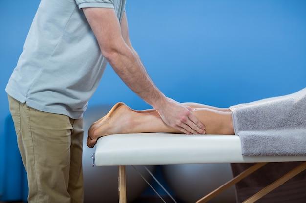 Fisioterapeuta masculino dando masaje de rodilla a paciente femenino