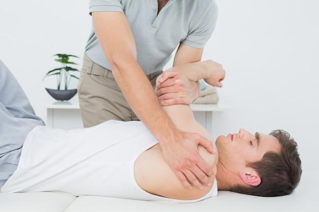 Fisioterapeuta masculino examinando una mano mans