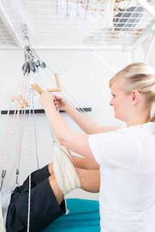 Fisioterapeuta con paciente en camilla.