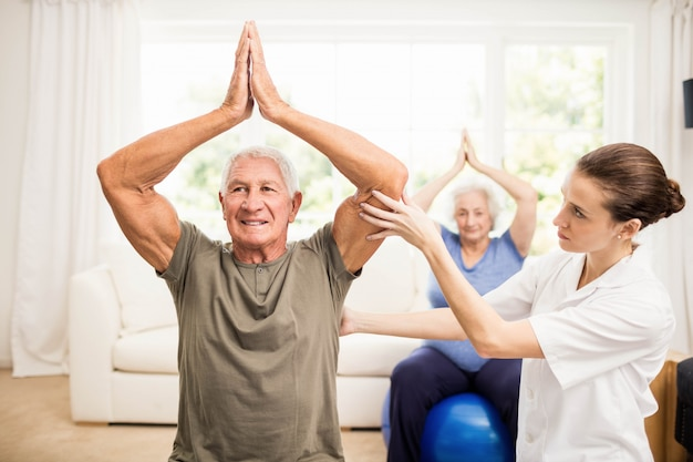 Fisioterapeuta que atiende a pacientes ancianos enfermos en el hogar