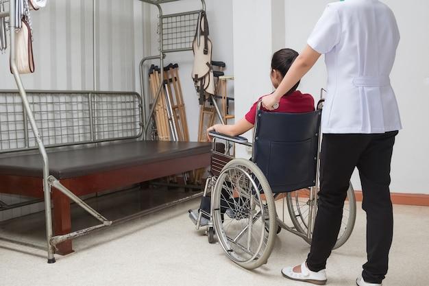 Fisioterapeuta que ayuda a la transferencia paciente de la mujer en la silla de ruedas