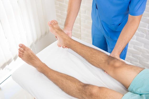 Fisioterapeuta que da la cura del tratamiento para el paciente de la pierna de brokien
