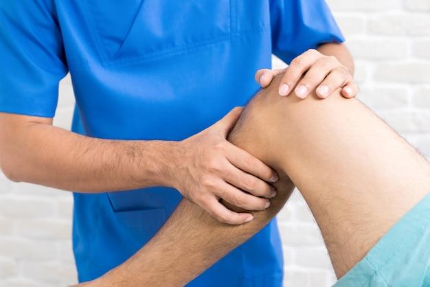 Fisioterapeuta que trata la rodilla lesionada de un paciente masculino en el hospital