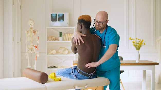 Fisioterapeuta realizando una sesión de terapia con un anciano en un centro de rehabilitación fí ...