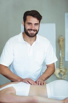 Fisioterapeuta sonriente dando masaje a una mujer
