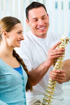 Fisioterapeuta en su práctica, explica a una paciente la columna vertebral y la aparición del dolor de espalda.