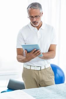 Fisioterapeuta con tableta digital en casa