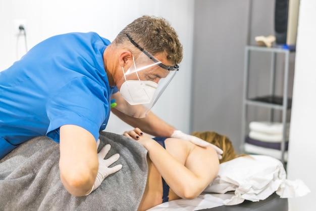 Fisioterapeuta vistiendo una mascarilla y escudo dando masaje de espalda a una paciente